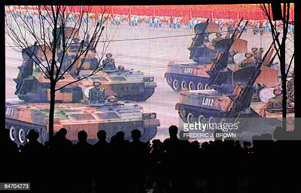 People gather on a sidewalk in Xining on February 7 2009 in northwest China's Qinghai province watching from a big screen televised footage of the...