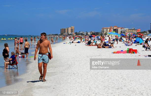 People gather on Clearwater Beach during spring break despite world health officials' warnings to avoid large groups on March 18, 2020 in Clearwater,...
