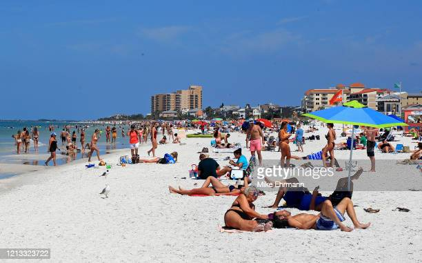 People gather on Clearwater Beach during spring break despite world health officials' warnings to avoid large groups on March 18 2020 in Clearwater...