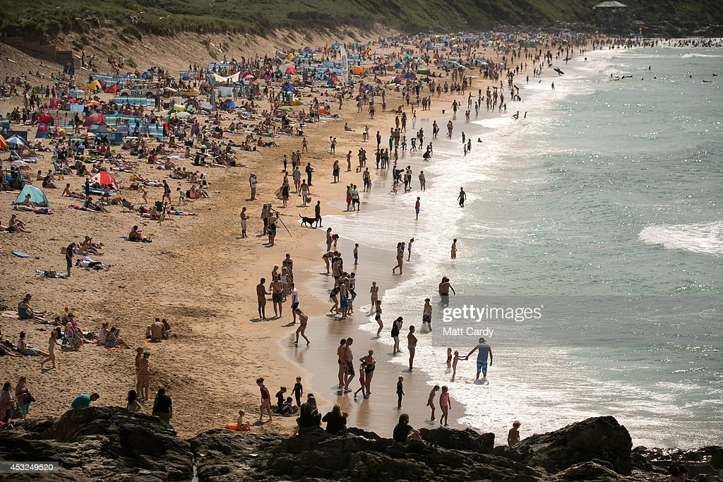 People gather on Fistral Beach on the first day of the Boardmasters surf and music festival in Newquay on August 6, 2014 in Cornwall, England. Since 1981, Newquay has been playing host to the Boardmasters surfing competition - which is part of a larger five-day surf, skate and music festival and has become a integral part of the continually popular British surf scene growing from humble beginnings, to one of the biggest events on the British surfing calendar. It now attracts professional surfers from across the globe to compete on the Cornish beach that is seen by many as the birthplace of modern British surfing.