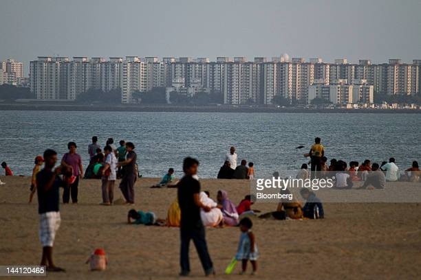 People gather on Girgaon Chowpatty beach across from residential buildings in Mumbai India on Wednesday May 9 2012 Mumbai is India's most expensive...