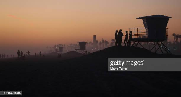 People gather on Huntington Beach which remains open amid the coronavirus pandemic at dusk on April 23 2020 in Huntington Beach California...