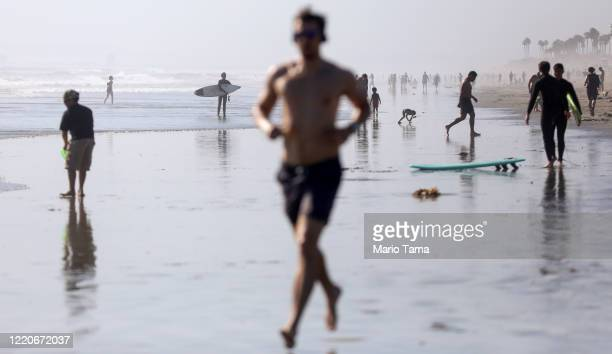 People gather on Huntington Beach which remains open amid the coronavirus pandemic on April 23 2020 in Huntington Beach California Neighboring...