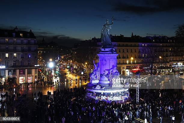 TOPSHOT People gather on January 10 2016 near the illuminated statue of the Republique at the Place de la Republique square during a remembrance...