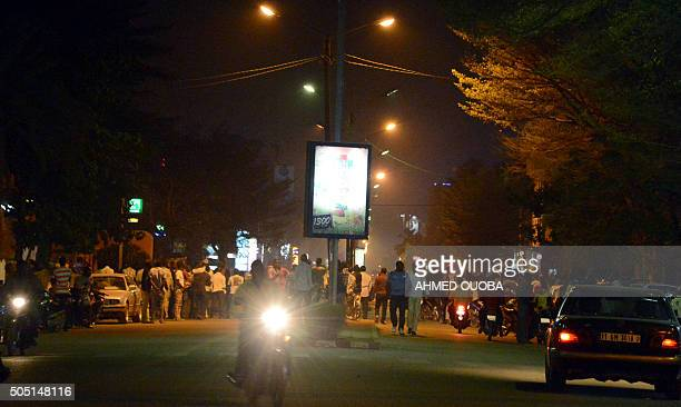 People gather on Kwame Nkruma avenue near Hotel Splendid where the attackers remain with sporadic gunfire continuing in Burkina Faso's capital...
