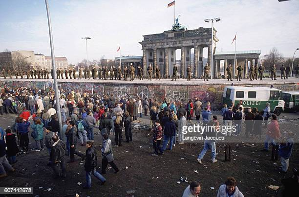 People gather on one side of the Berlin Wall as German soldiers stand on a raised platform before the Brandenburg gate during the destruction of the...