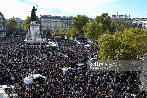 People gather on Place de la Republique in Paris on October 18 in homage to history teacher Samuel Paty two days after he was beheaded by an attacker...
