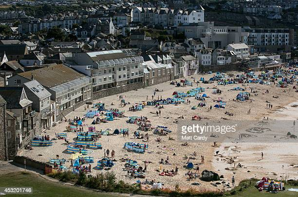 People gather on Porthmeor Beach overlooked by the Tate on August 4 2014 in St Ives Cornwall England A recent survey by the online hotel booking...