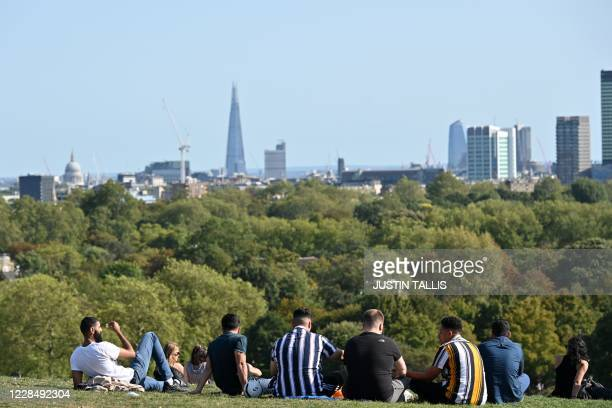People gather on Primrose Hill in central London in the late summer sunshine on September 13 the day before the UK government brings in tightened...
