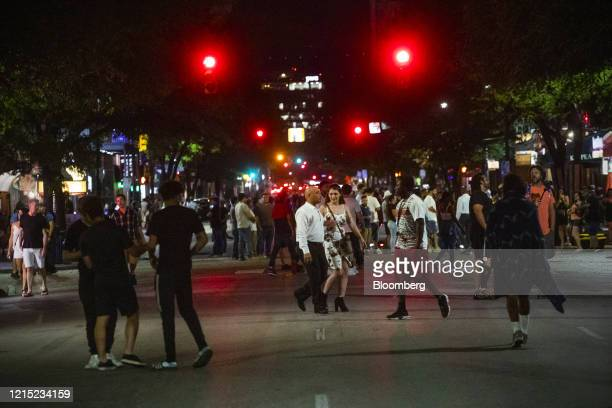 People gather on Sixth Street at night in Austin, Texas, U.S., on Saturday, May 23, 2020. Texas bars, bowling alleys and other businesses were able...