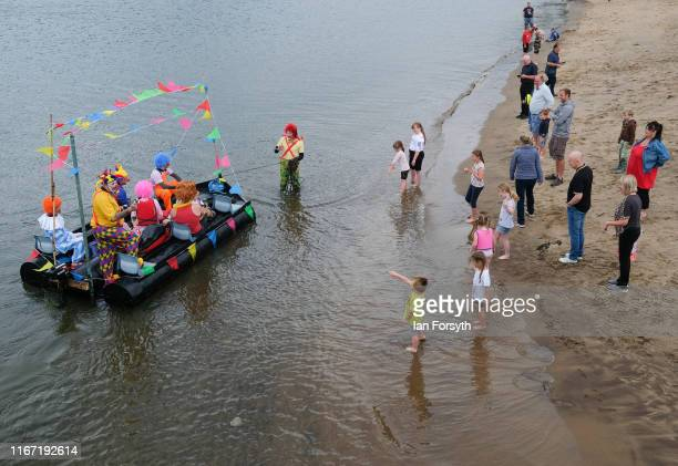 People gather on the beach as a raft carrying people dressed as clowns heads to shore during the annual Whitby Regatta on August 10 2019 in Whitby...