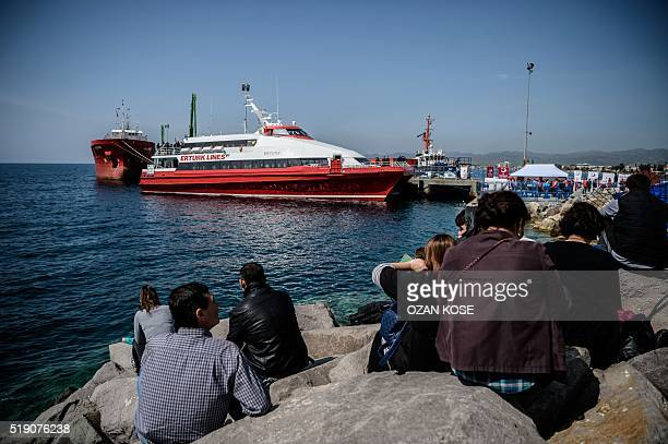 People gather on the beach as migrants deported from Greece arrive aboard a small Turkish ferry in the port of Dikili district in Izmir Turkey on...