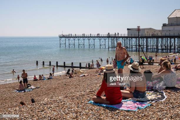 People gather on the beach by the pier during the warm weather on Bank Holiday Monday on May 7, 2018 in Bognor Regis, United Kingdom. Britons across...