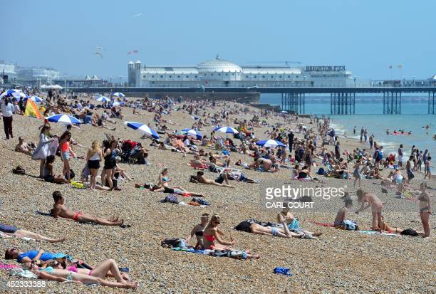 People gather on the beach in Brighton on July 18 as parts of the country were expected to experience the hottest day of the year so far and the Met...