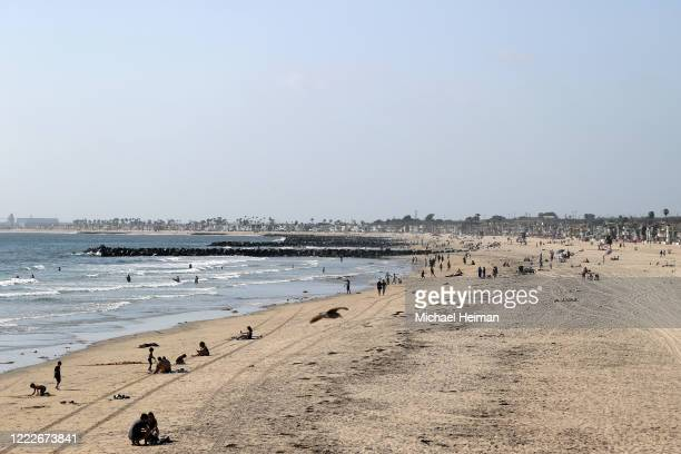 People gather on the beach north of Newport Pier on May 3 2020 in Newport Beach California California Gov Gavin Newsom ordered all beaches in the...