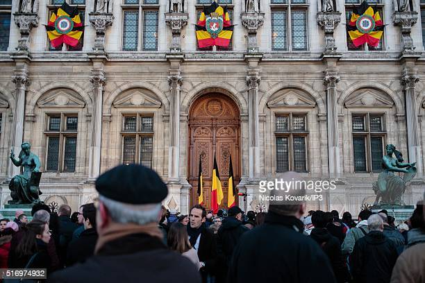 People gather on the front of the Hotel de Ville to pay tribute to the victims of the terrorists attacks in Belgium on March 22 2016 in Paris France...