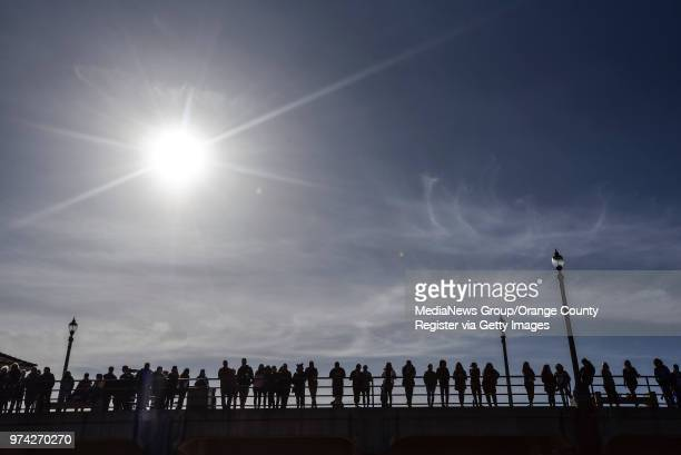 People gather on the Huntington Beach Pier during the start of a paddle out to honor Pierre Agnes CEO of Quiksilver in Huntington Beach on Friday Mar...