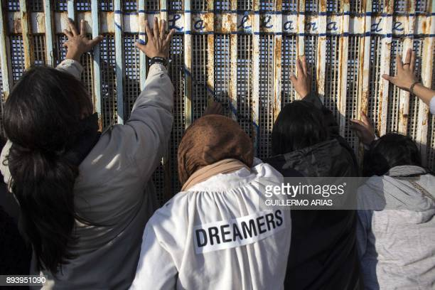 People gather on the Mexican side of the border fence to touch hands during the celebration of the Posada Sin Fronteras or Posada Without Borders at...