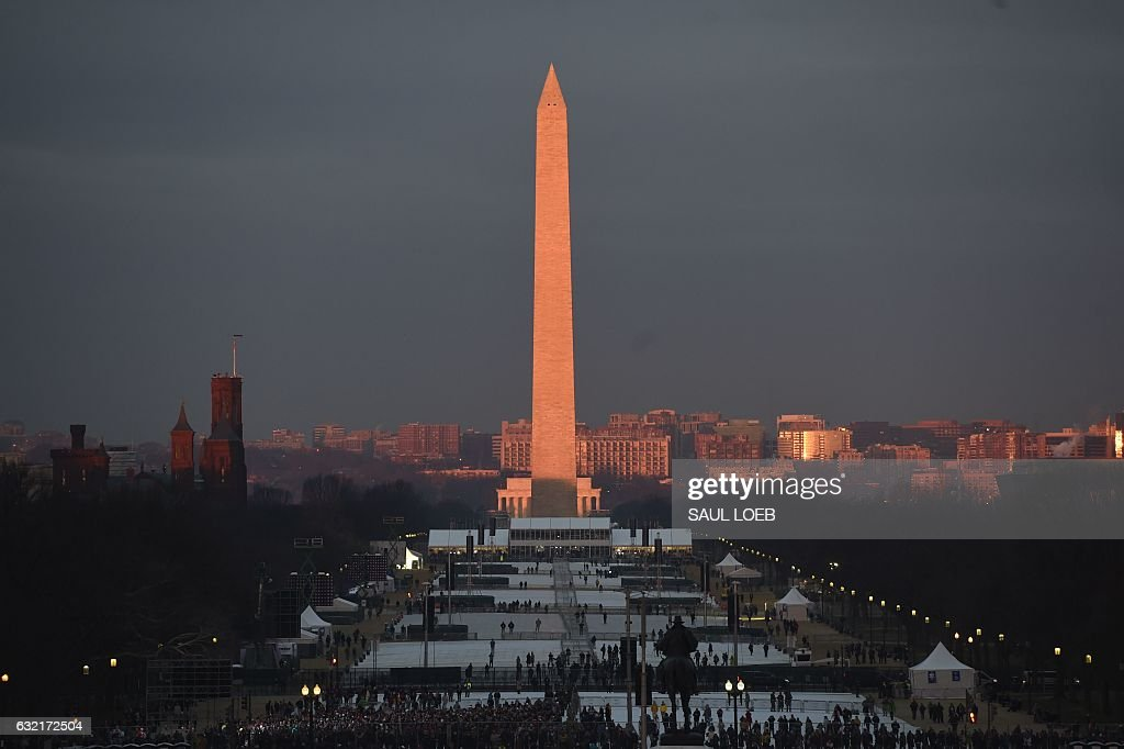 TOPSHOT - People gather on the National Mall in Washington, DC, on January 20, 2017, before the inauguration of US President-elect Donald Trump. / AFP / POOL / SAUL