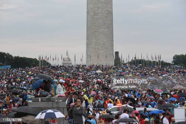 People gather on the National Mall while President Donald Trump gives his speech during Fourth of July festivities on July 4 2019 in Washington DC...