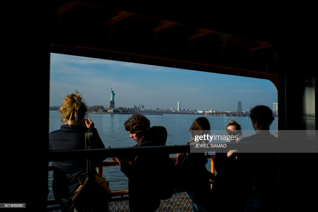 TOPSHOT - People gather on the outer deck on a Staten Island ferry as it sails towards Manhattan, passing the Statue of Liberty on February 20, 2018, in New York. / AFP PHOTO / Jewel SAMAD