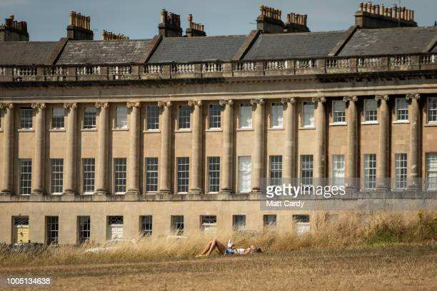 People gather on the parched grass in front of the Royal Crescent on July 25 2018 in Bath England The lack of rainfall over the last few weeks...