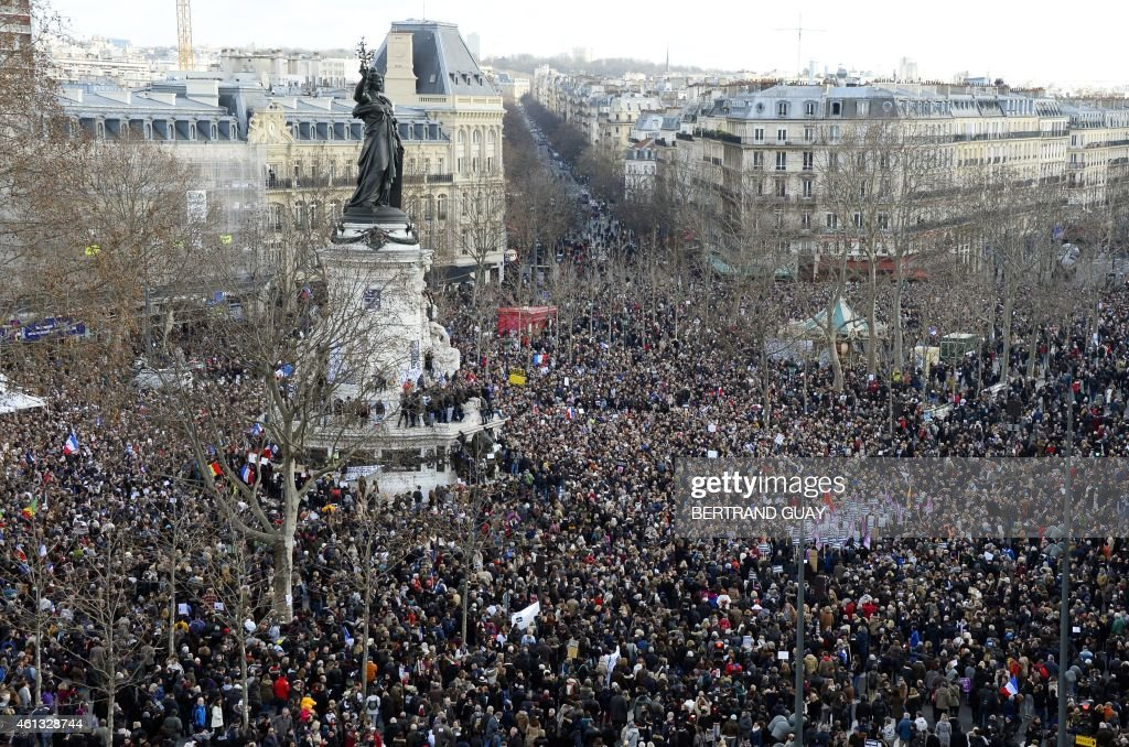 People gather on the Place de la Republique (Republic Square) in Paris before the start of a Unity rally Marche Republicaine on January 11, 2015 in tribute to the 17 victims of a three-day killing spree by homegrown Islamists. The killings began on January 7 with an assault on the Charlie Hebdo satirical magazine in Paris that saw two brothers massacre 12 people including some of the country's best-known cartoonists, the killing of a policewoman and the storming of a Jewish supermarket on the eastern fringes of the capital which killed 4 local residents.
