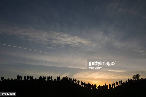 People gather on the ridge overlooking the Avebury Neolithic henge monument a UNESCO World Heritage site as they wait to see the sun rise on June 21...