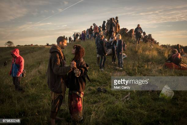 People gather on the ridge overlooking the Avebury Neolithic henge monument a UNESCO World Heritage site as they watch the sun rise on June 21 2018...