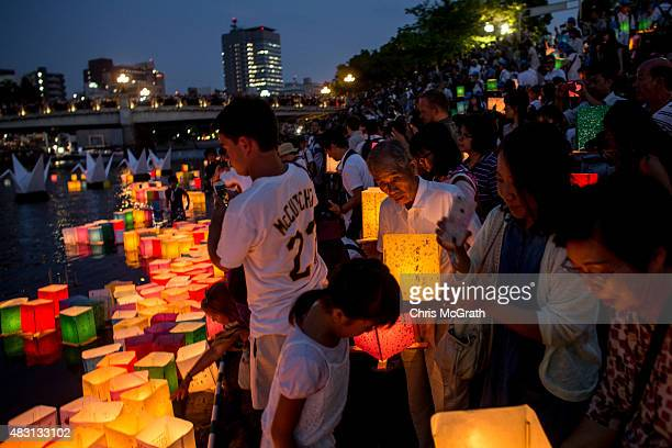 People gather on the rivers edge to float candle lit paper lanterns during 70th anniversary activities commemorating the atomic bombing of Hiroshima...