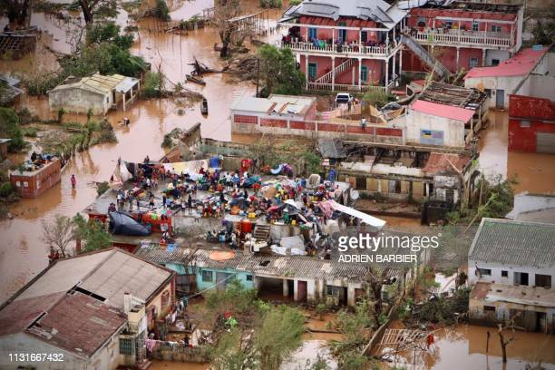 People gather on the roof of a house submerged by floods in Buzi on March 20 2019 International aid agencies raced on March 20 to rescue survivors...