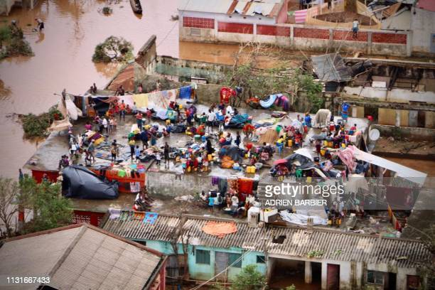 People gather on the roof of a house submerged by floods in Buzi on March 20, 2019. - International aid agencies raced on March 20 to rescue...