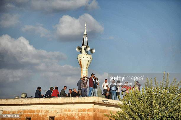 People gather on the roof of a mosque as the watch the air strike by the USled coalition in Kobani on October 25 2014 in Sanliurfa province Turkey...