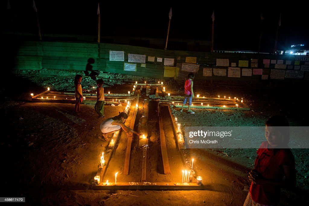 TACLOBAN, LEYTE, PHILIPPINES - NOVEMBER 08: People gather on the street around candles shaped in a cross during the candlelight memorial on November 8, 2014 in Tacloban, Leyte, Philippines. People lined the roads with candles all across Tacloban from the airport to downtown in remembrance of the victims of Typhoon Haiyan. Residents and typhoon survivors from across the central Philippines attended memorial services, candlelight vigils and visited mass graves honouring those who lost their lives one year ago when Typhoon Haiyan, the strongest typhoon ever to make landfall swept across the region, leaving more than 6000 dead and many more homeless.