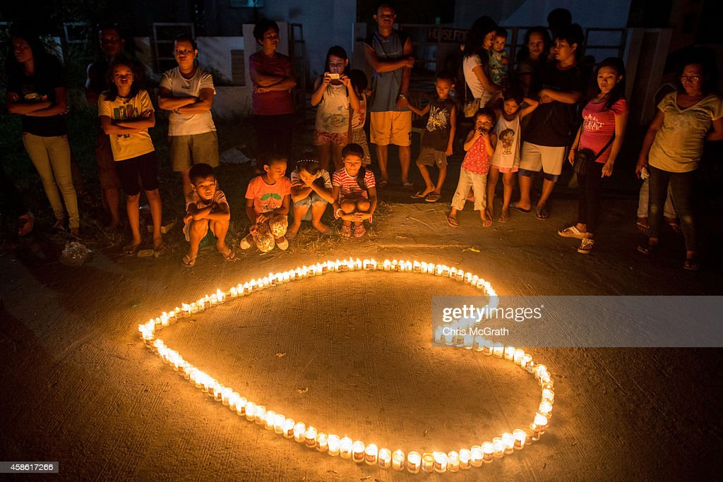 TACLOBAN, LEYTE, PHILIPPINES - NOVEMBER 08: People gather on the street around candles shaped in a heart during the candlelight memorial on November 8, 2014 in Tacloban, Leyte, Philippines. People lined the roads with candles all across Tacloban from the airport to downtown in remembrance of the victims of Typhoon Haiyan. Residents and typhoon survivors from across the central Philippines attended memorial services, candlelight vigils and visited mass graves honouring those who lost their lives one year ago when Typhoon Haiyan, the strongest typhoon ever to make landfall swept across the region, leaving more than 6000 dead and many more homeless.