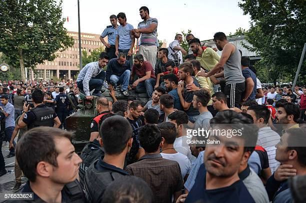 People gather on the top of a Turkish military tank early in the morning July 16 2016 in Ankara Turkey Istanbul's bridges across the Bosphorus the...