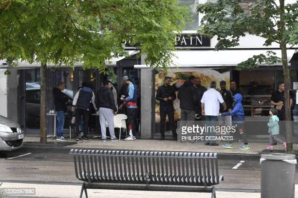 People gather outside a bar in the Gresilles area of Dijon, eastern France, on June 17 as new tensions flared in the city after it was rocked by a...