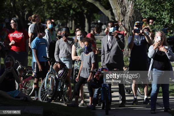 People gather outside a house where Democratic presidential nominee Joe Biden and his wife Dr. Jill Biden participate in a conversation with parents...