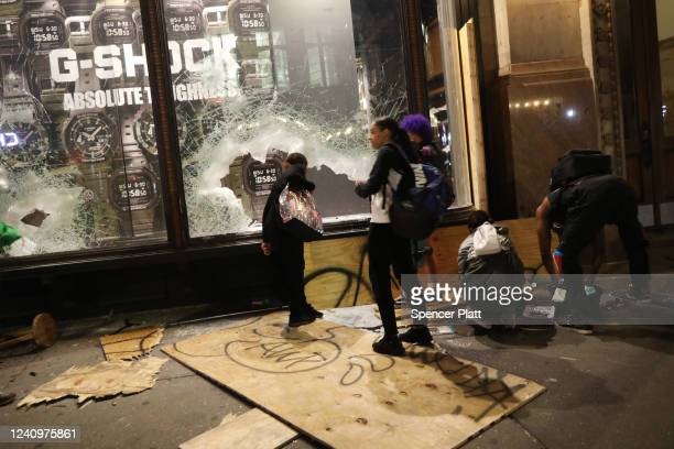 People gather outside a looted store on Broadway during a night of protests and vandalism over the death of George Floyd on June 1 2020 in New York...