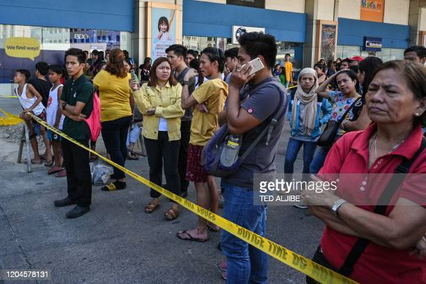 People gather outside a mall after a hostage situation was reported in suburban Manila on March 2, 2020. - Heavily armed police were deployed at the...