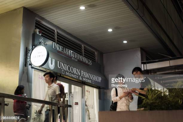 People gather outside a money changer and pawnshop at night in the San Antonio Village area of Makati City Manila the Philippines on Wednesday May 2...