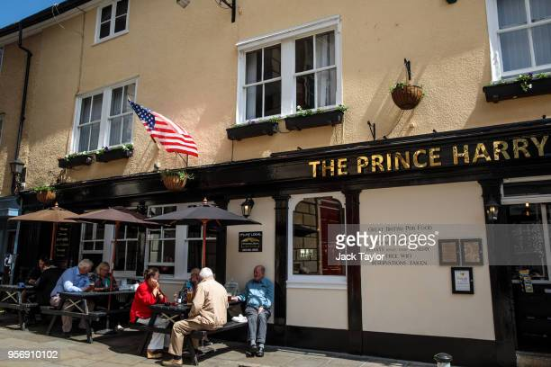 People gather outside a pub called The Prince Harry underneath a US flag ahead of the wedding of Prince Harry and his fiance US actress Meghan Markle...