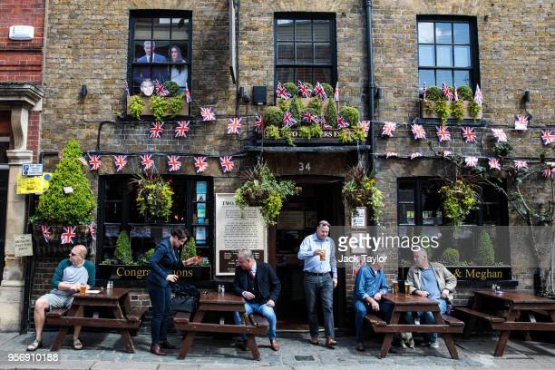 People gather outside a pub decorated to mark the upcoming wedding of Prince Harry and his fiance US actress Meghan Markle on May 10 2018 in Windsor...