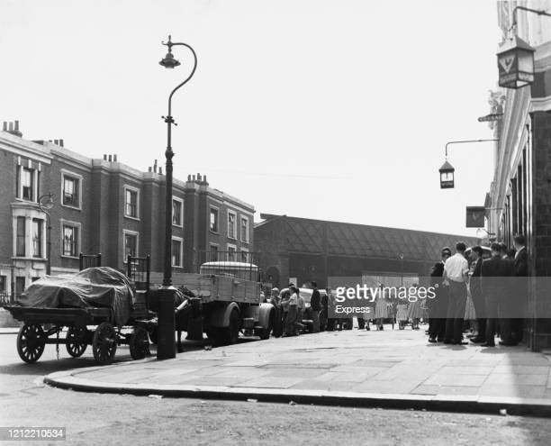 People gather outside a public house the morning following one of the race riots in Notting Hill, London, UK, 1st September 1958.