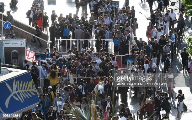 People gather outside de festival palace on May 8 2018 before the opening ceremony of the 71st edition of the Cannes Film Festival in Cannes southern...