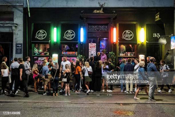 People gather outside Ibiza Beach Bar, in Copenhagen, Denmark, on August 21, 2020 as the government demanded that bars keep their doors closed for...