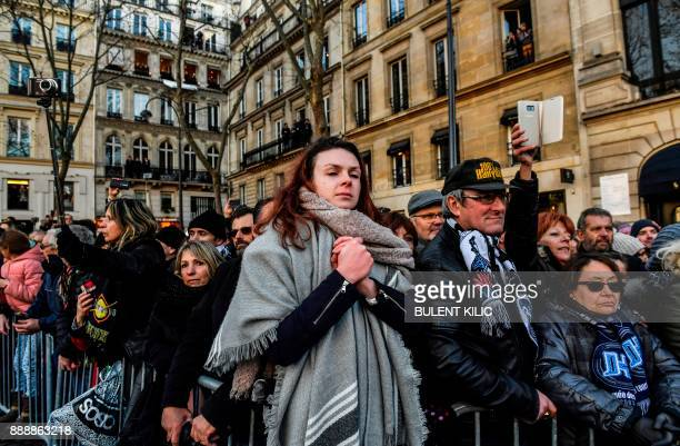 People gather outside La Madeleine Church during the funeral ceremony in tribute to late French singer Johnny Hallyday on December 9 2017 in Paris...