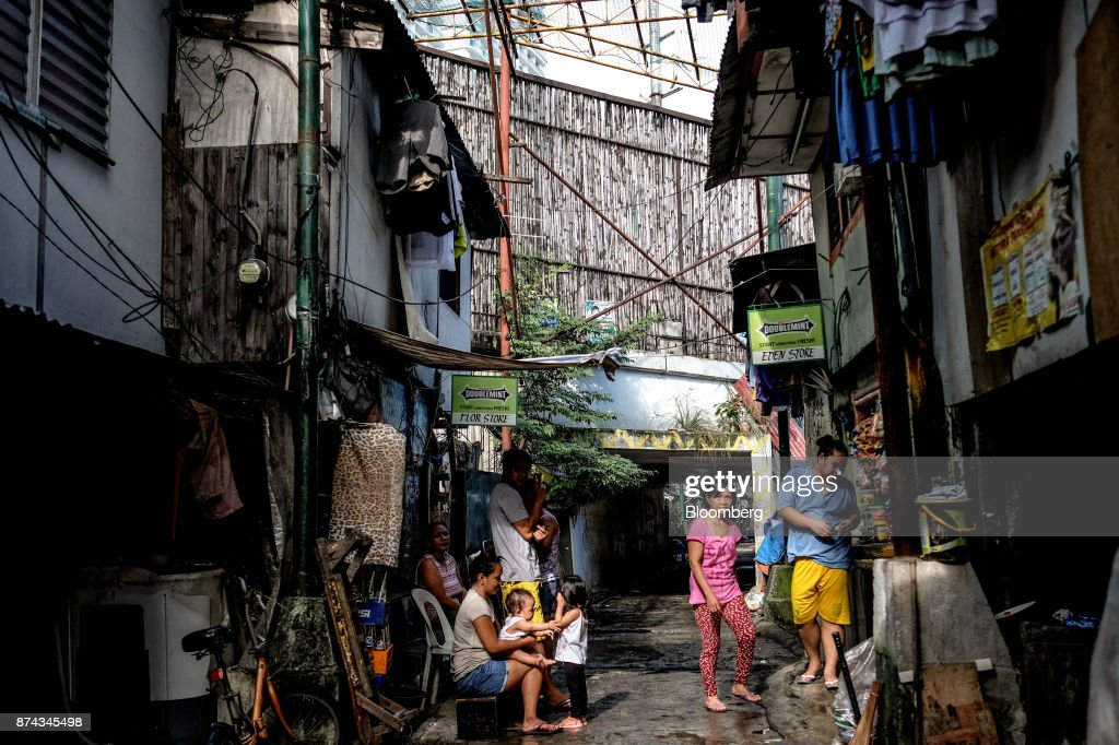 People gather outside low-cost housing in Mandaluyong, Metro Manila, Philippines, on Tuesday, Nov. 14, 2017. Economists are forecasting the Philippines to be among the first to raise interest rates in the region and the International Monetary Fund saidlast week the central bank should be ready to tighten if there are signs of overheating. Photographer: Veejay Villafranca/Bloomberg via Getty Images