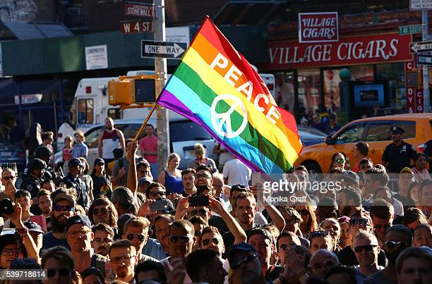 People gather outside of the Stonewall Inn as a vigil is held following the massacre that occurred at a gay Orlando nightclub on June 12, 2016 in New...