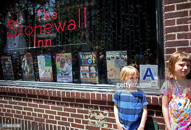 People gather outside of the Stonewall Inn June 26 2015 in the West Village neighborhood in New York City The iconic gay bar was recently granted...